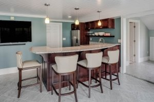 Basement Kitchen Bar area Dark Cabinetry and light granite countertops
