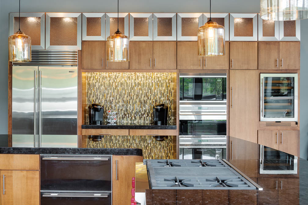 Remodeled kitchen with wooden cabinets, steel accents, and gold backsplash