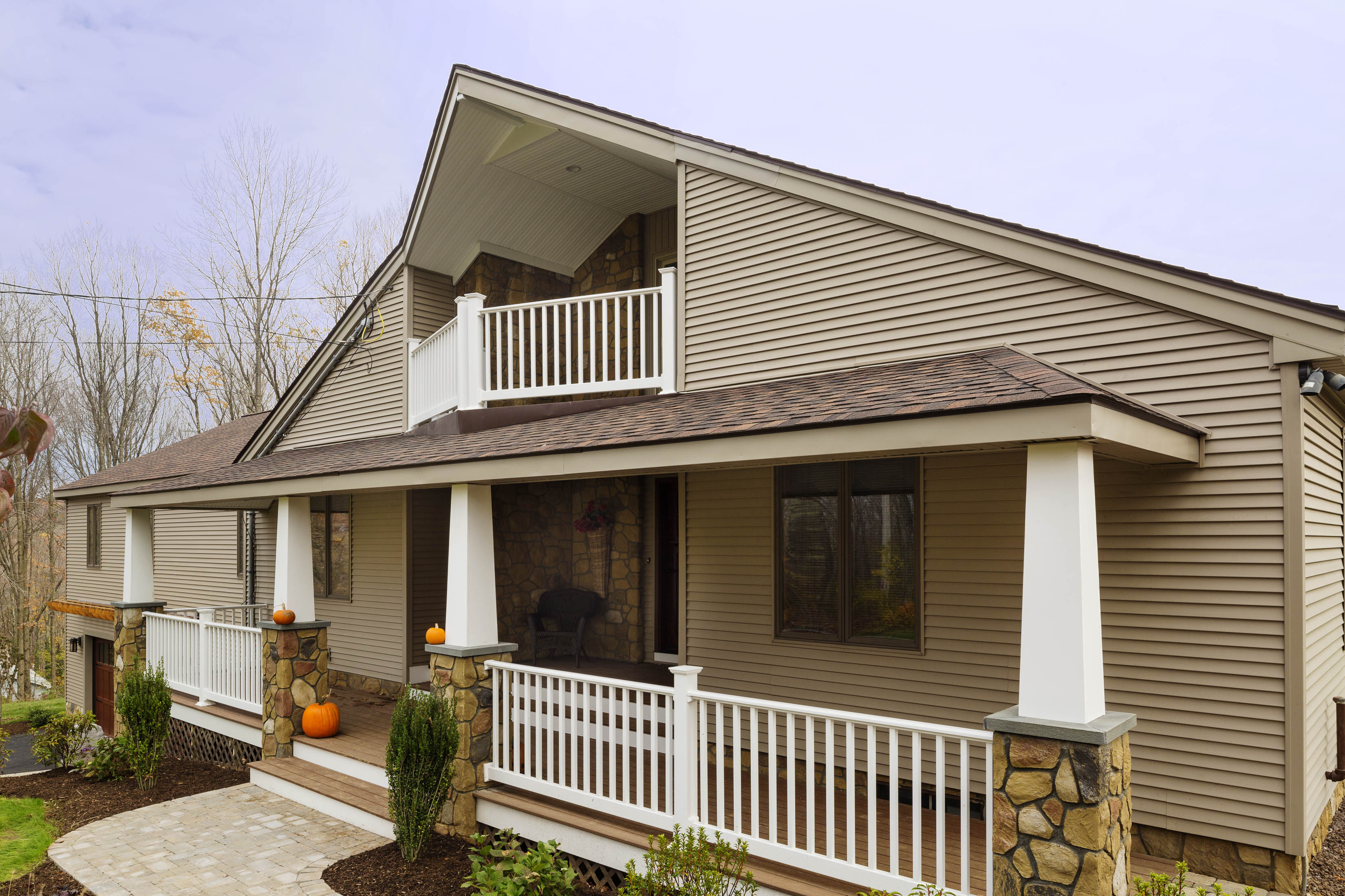 House with brown siding, stone pillars, and sloped roof